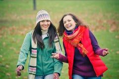 Mujer joven dos que recorre en parque del otoño Imagen de archivo libre de regalías