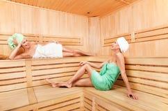 Mujer joven dos que se relaja en sauna Imagen de archivo libre de regalías