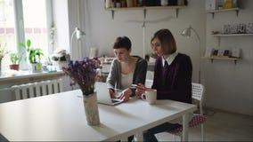 Mujer joven dos que se sienta en la tabla y que usa el cuaderno para la orden en línea metrajes