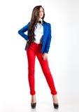 Mujer joven dulce en pantalones rojos y capa azul Fotografía de archivo