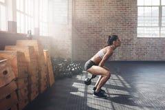 Mujer joven dura que ejercita con la campana de la caldera en el gimnasio Fotografía de archivo libre de regalías
