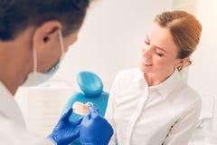Mujer joven durante la consulta en la clínica dental fotos de archivo