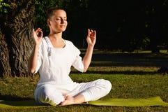 Mujer joven durante la meditación de la yoga en el parque Foto de archivo libre de regalías