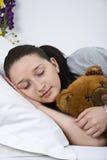 Mujer joven durmiente con el oso de peluche Foto de archivo
