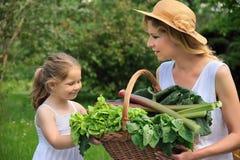 Mujer joven e hija con las verduras frescas Fotos de archivo libres de regalías