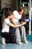 Mujer joven e instructor en la gimnasia Fotos de archivo libres de regalías