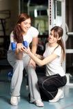 Mujer joven e instructor en la gimnasia Foto de archivo libre de regalías