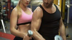 Mujer joven e instructor que hacen ejercicio de elevación de la pesa de gimnasia junto en el gimnasio metrajes