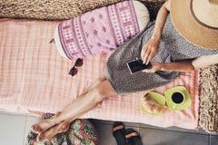 Mujer joven el vacaciones usando el teléfono elegante foto de archivo