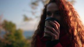 Mujer joven elegante alegre en la bufanda roja de la capa que se coloca al aire libre en el café de consumición de la calle en lu almacen de video