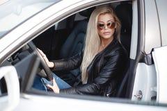 Mujer joven elegante con el pelo rubio largo que se sienta en el asiento del ` s del conductor de un coche prestigioso fotos de archivo
