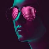 Mujer joven elegante en gafas de sol con la lente rosada fotografía de archivo