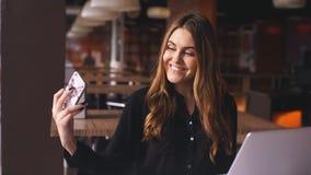 Mujer joven elegante en la camisa negra que se sienta en el café y que toma el selfie con su teléfono elegante almacen de video