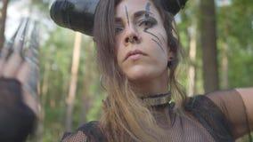 Mujer joven elegante en trajes de teatro del diablo o del baile maléfico en funcionamiento de la demostración del bosque o ritual almacen de video