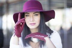 Mujer joven elegante en un sombrero y los guantes de Borgoña Imágenes de archivo libres de regalías
