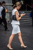 Mujer joven elegante que camina y que comprueba su teléfono foto de archivo