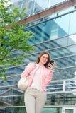 Mujer joven elegante que envía el mensaje de texto en el teléfono móvil Imagenes de archivo