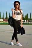 Mujer joven elegante que lleva el sombrero negro y la mochila que modelan en la calle Imágenes de archivo libres de regalías