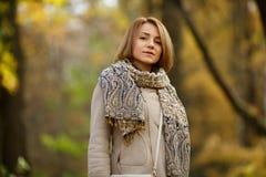 Mujer joven elegante que lleva la ropa caliente que presenta en bosque del otoño Imágenes de archivo libres de regalías