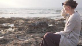 Mujer joven elegante que se sienta en una costa rocosa metrajes