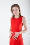 Mujer joven embarazada con la muestra del corazón Imágenes de archivo libres de regalías