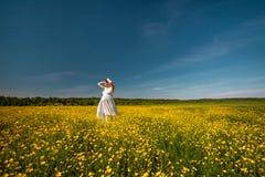 Mujer joven embarazada de la belleza en el vestido blanco en el prado de la luz del sol fotografía de archivo