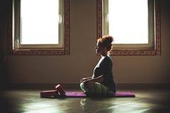 Mujer joven embarazada de la cabeza roja en la clase de la yoga interior Fotos de archivo