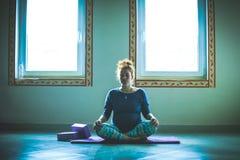 Mujer joven embarazada de la cabeza roja en la clase de la yoga interior Foto de archivo