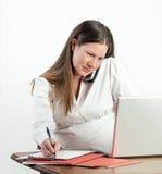 Mujer joven embarazada en el teléfono en el ordenador portátil en la oficina o el hogar Imágenes de archivo libres de regalías