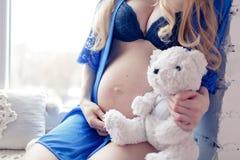 Mujer joven embarazada feliz que espera a un niño Imagenes de archivo