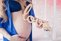 Mujer joven embarazada feliz que espera a un niño Fotos de archivo