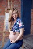 Mujer joven embarazada feliz que espera a un niño Imágenes de archivo libres de regalías