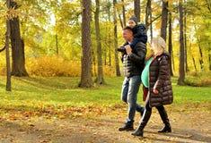 Mujer joven embarazada que camina en parque del otoño con su marido y niño Fotos de archivo