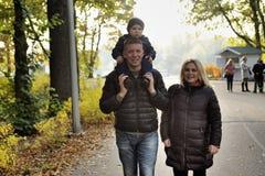 Mujer joven embarazada que camina en parque del otoño con su marido y niño Imagen de archivo libre de regalías