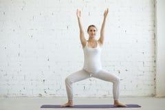 Mujer joven embarazada que hace yoga prenatal Actitud de la posición en cuclillas del sumo Foto de archivo libre de regalías