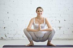 Mujer joven embarazada que hace yoga prenatal Guirnalda, actitud de Malasana Imagenes de archivo