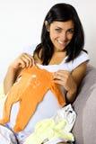 Mujer joven embarazada que muestra la ropa del bebé Fotografía de archivo
