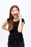 Mujer joven emocionada alegre que habla en el teléfono celular Fotografía de archivo