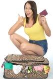 Mujer joven emocionada contenta feliz que se arrodilla detrás de una maleta que sostiene un pasaporte Imagenes de archivo