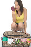 Mujer joven emocionada contenta feliz que se arrodilla detrás de una maleta que sostiene un pasaporte Fotografía de archivo