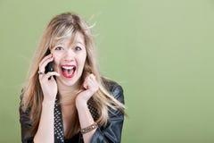 Mujer joven emocionada en el teléfono Fotos de archivo libres de regalías