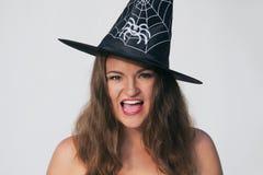 Mujer joven emocionada en sombrero de la bruja de Halloween Foto de archivo libre de regalías