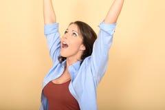 Mujer joven emocionada feliz con las manos aumentadas emocionadas Foto de archivo libre de regalías