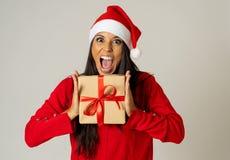 Mujer joven emocionada loca feliz en el sombrero de Papá Noel con el regalo de Navidad que ríe y que sonríe imagen de archivo