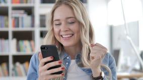 Mujer joven emocionada para el éxito en Smartphone almacen de video