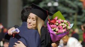 Mujer joven emocionada que abraza al pariente masculino feliz, enhorabuena en la graduación almacen de metraje de vídeo