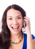 Mujer joven emocionada que habla en el teléfono celular Foto de archivo