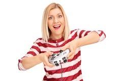 Mujer joven emocionada que juega a los videojuegos Foto de archivo
