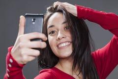 Mujer joven emocionada que le toma el selfie con el teléfono celular Foto de archivo