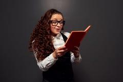 Mujer joven emocionada que lee el libro Foto de archivo libre de regalías